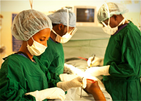 A close up shot of two doctors at CURE Uganda in the operating theater. In the background there is an x-ray of the head of a child who has hydrocephalus
